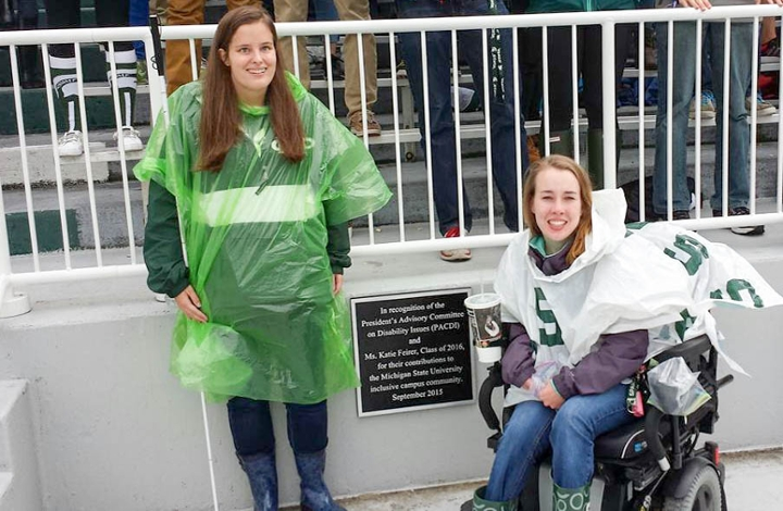 Katie Feirer (right) and senior Jordyn Castor (left) pose with the plaque dedicated to Katie and PACDI for their efforts to make Spartan Stadium an inclusive community.